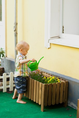 toddler watering the flowers barefoot in child garden in montessori school in berlin germany