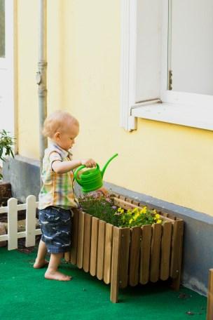 toddler watering the flowers barefoot in child garden in montessori school in berlin germany