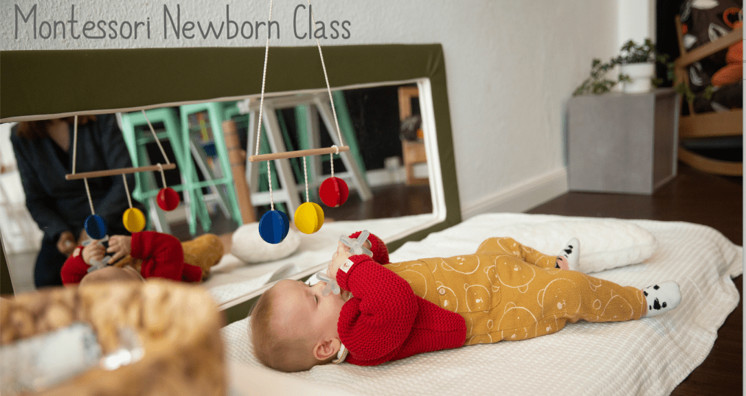 Montessori Newborn Class jn Berlin, Germany's first Montessori Early Learning Center, a Montessori school for parents and babies to use the Montessori approach together. Pictured is a baby using the interlocking discs tactile mobile in the movement area on a montessori mattress near the horizontal mirror.