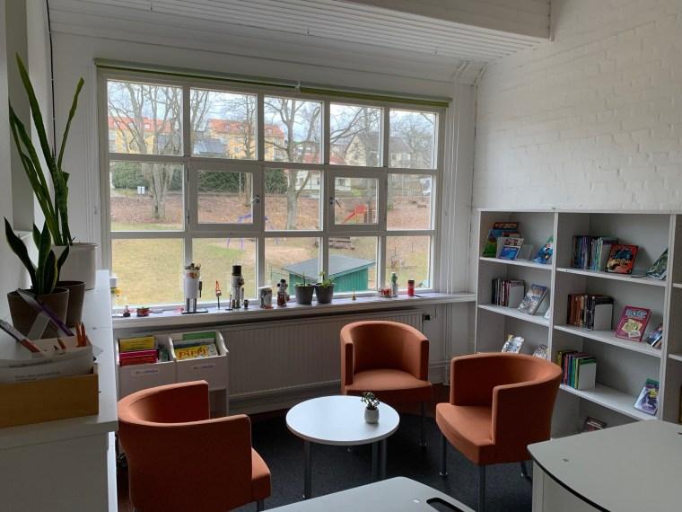 Skolans bibliotek med fåtöljer och bokhyllor framför ett stort fönster