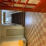Entréplanet i skolbyggnaden med röd- och vitrutigt stengolv och trappan upp till skolan.