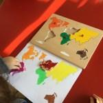 Ett barn ritar en världskarta med hjälp av pusselbitar