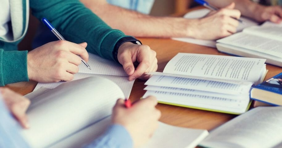 Stock image of students studying with books and other materials. (Syda Productions / Shutterstock)