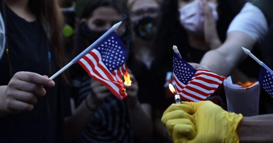"""Leftist activists burn American flags at an area designated as """"Black Lives Matter Plaza"""" near the White House in Washington on July 4, 2020."""