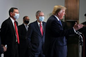 U.S. Senator John Barasso (R-WY) and Senate Majority Leader Mitch McConnell (R-KY) listen to U.S. President Donald Trump talk to reporters following a closed Senate Republican policy lunch meeting to discuss the response to the coronavirus disease (COVID-19) outbreak on Capitol Hill in Washington, U.S., May 19, 2020. REUTERS/Leah Millis