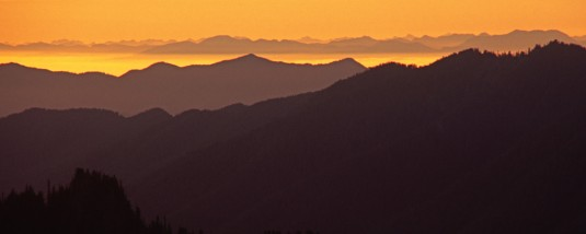A view of the distant mountains layered against the glowing golden sunset