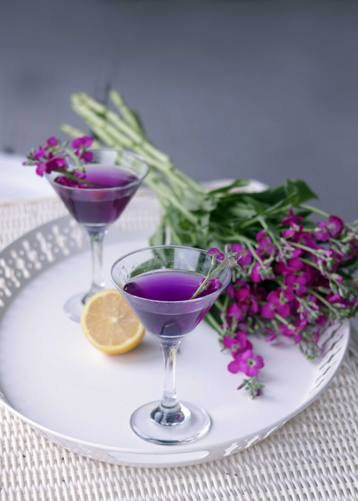 Purple martini with flower garnish.