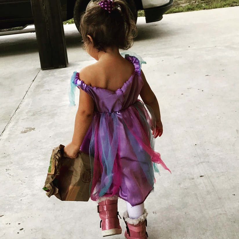 Little girl in a princess dress, furry boots, and a burger king bag.
