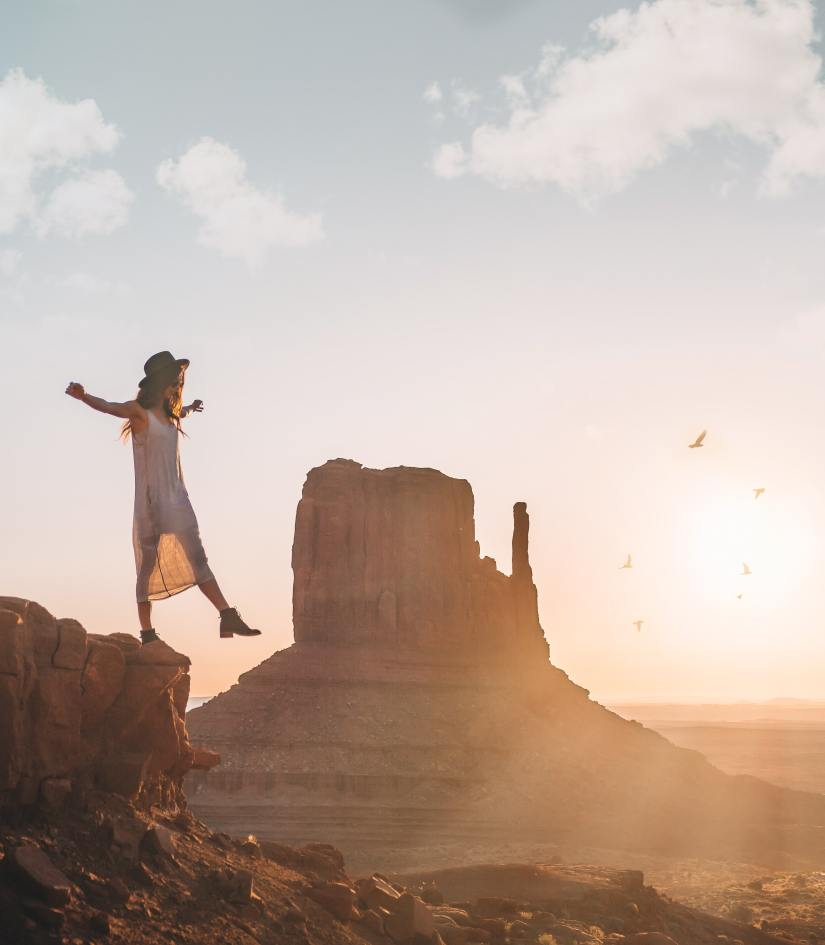 woman stepping off a small cliff in freedom