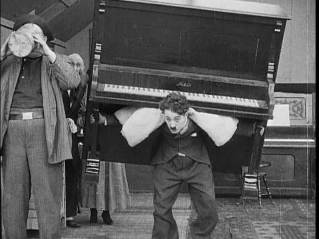 """Chaplin as the Piano Mover in """"His Musical Career."""""""