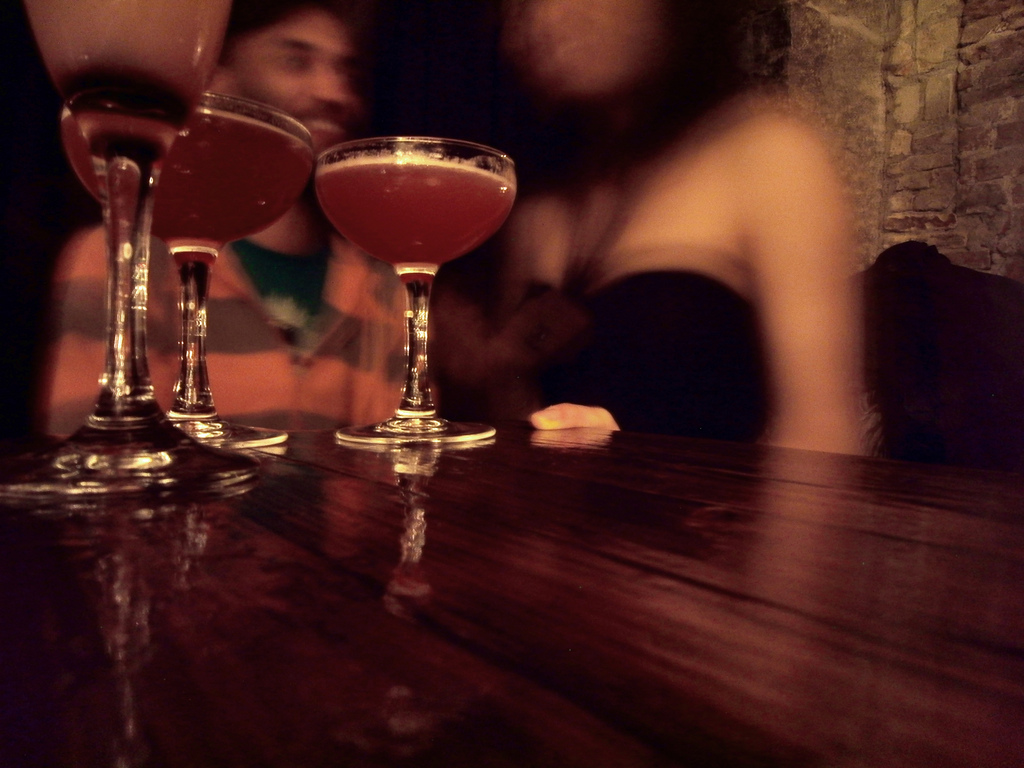 View of two cocktails on a glossy wood bar with indistinct figures in the background.