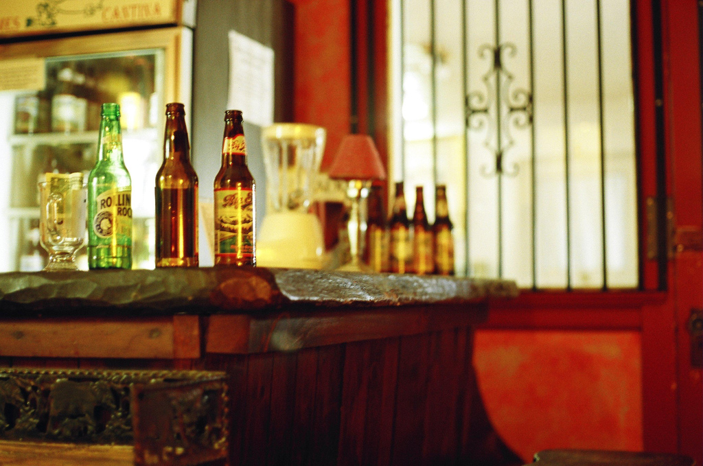 Beer bottles cluster on a heavy, rough-hewn wooden bar top.