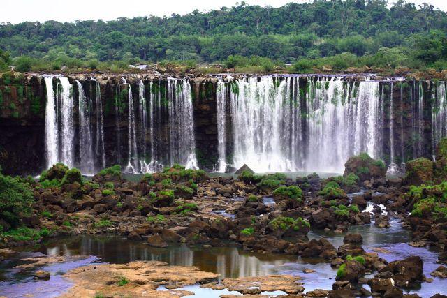 A long curtain of water spills over verdant cliffs.