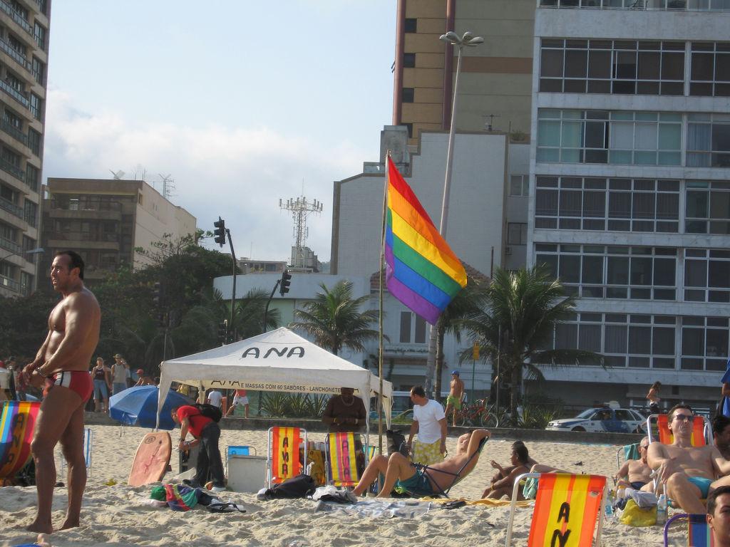 Beachgoers near a tent with a rainbow flag and beach chairs on the white sand of Ipanema beach.