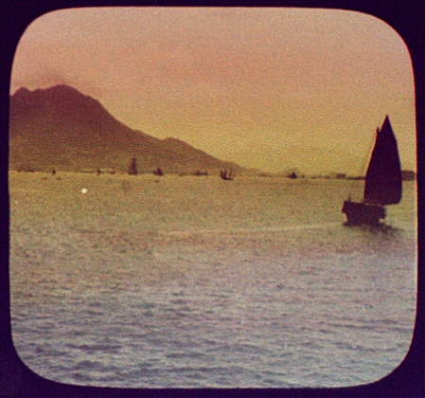 Grainy vintage photo of a sailboat on the ocean with land visible in the distance.
