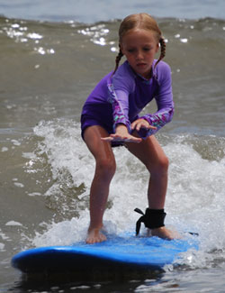 A young girl rides in to shore on a surfboard.
