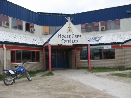 A dirt bike is parked in front of the simple modern building of the Moose Cree Complex.