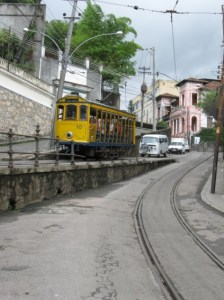 An aging yellow trolley on a winding street.