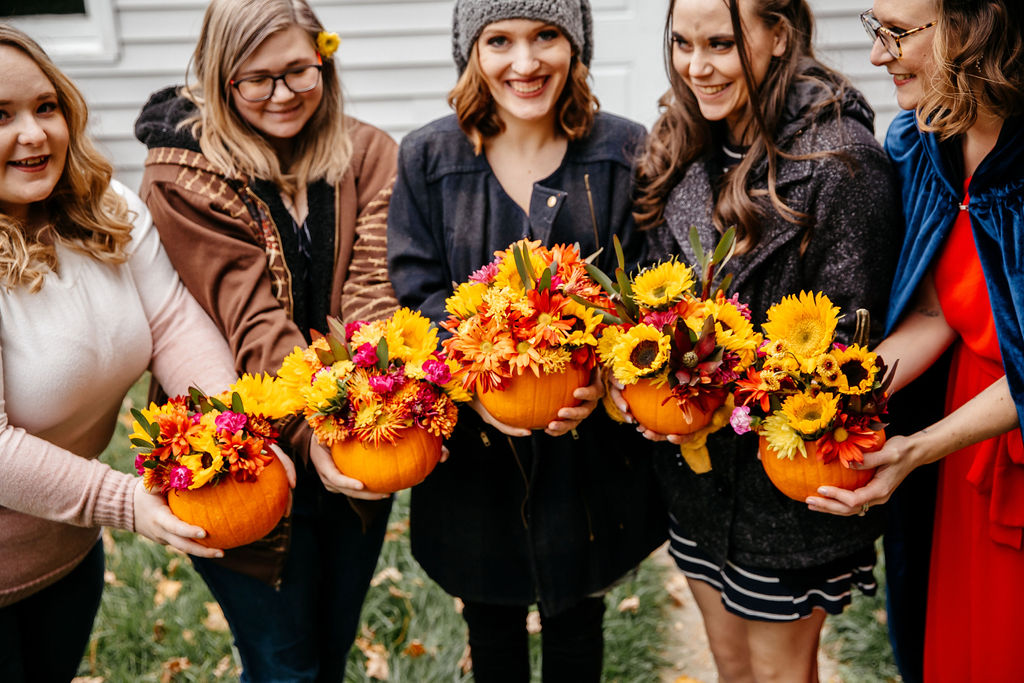 All the girls hold the pumpkin arrangements they learned to make