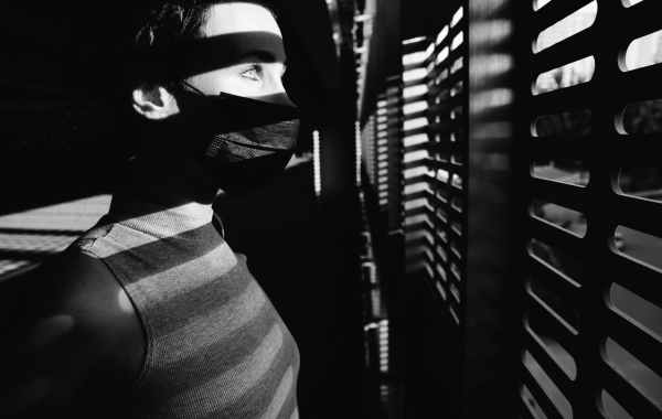 man wearing mask and looking out the window in quarantine during a pandemic