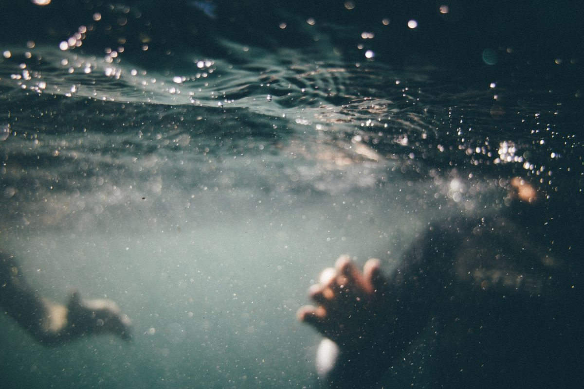 underwater person drowning in dark water