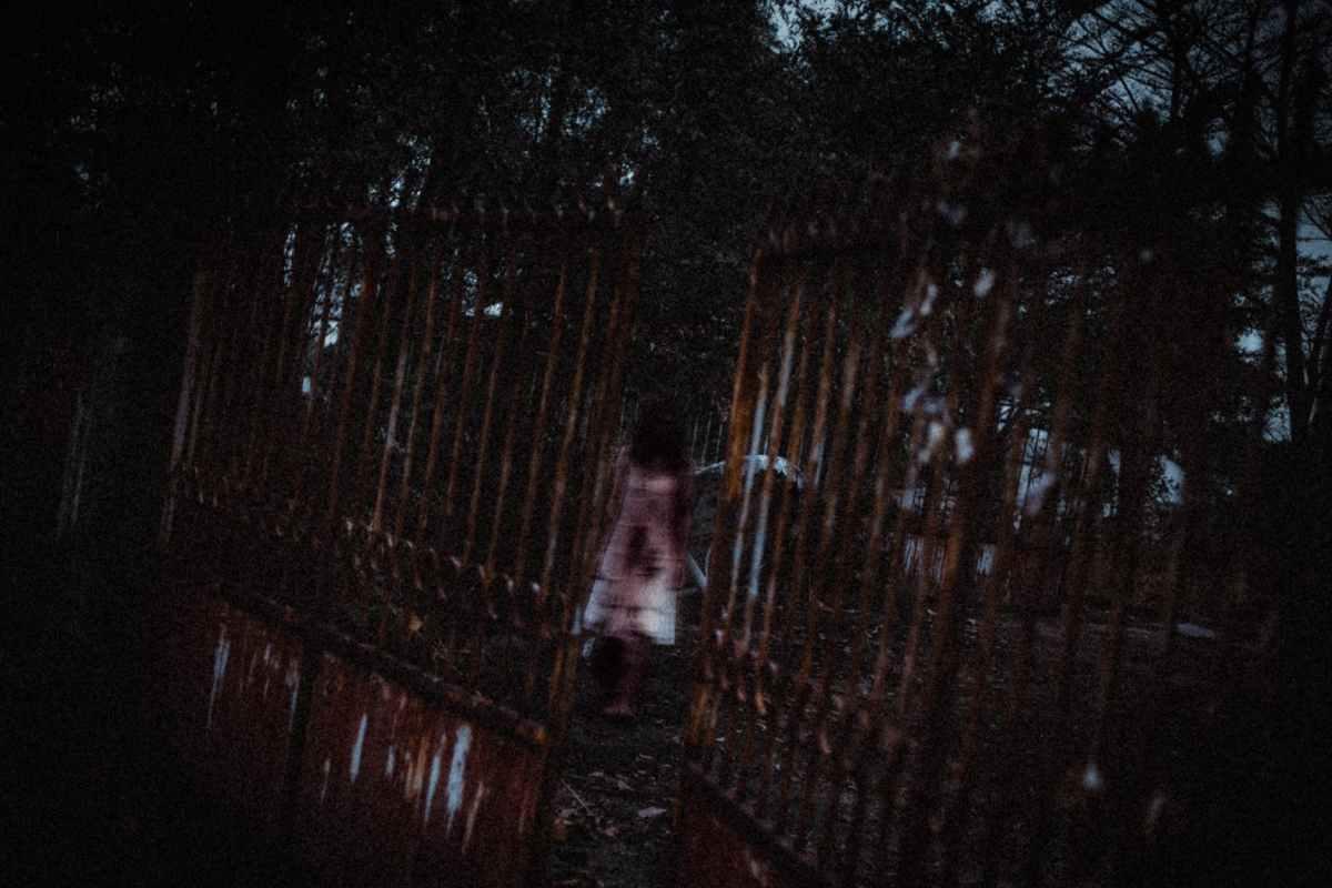 unrecognizable zombie woman walking in park near aged metal fence