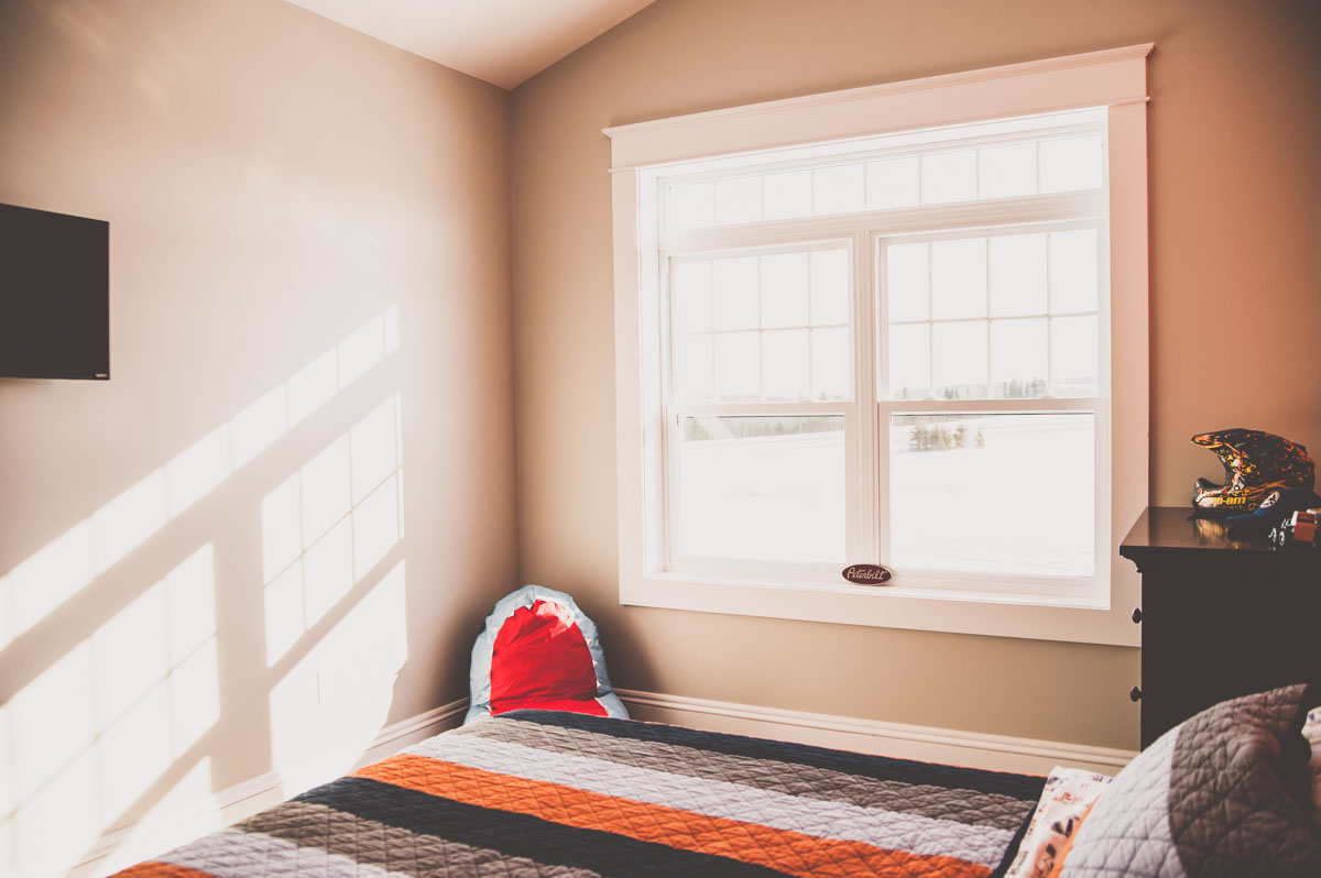 A bedroom featuring large windows and beautiful trim in bedroom