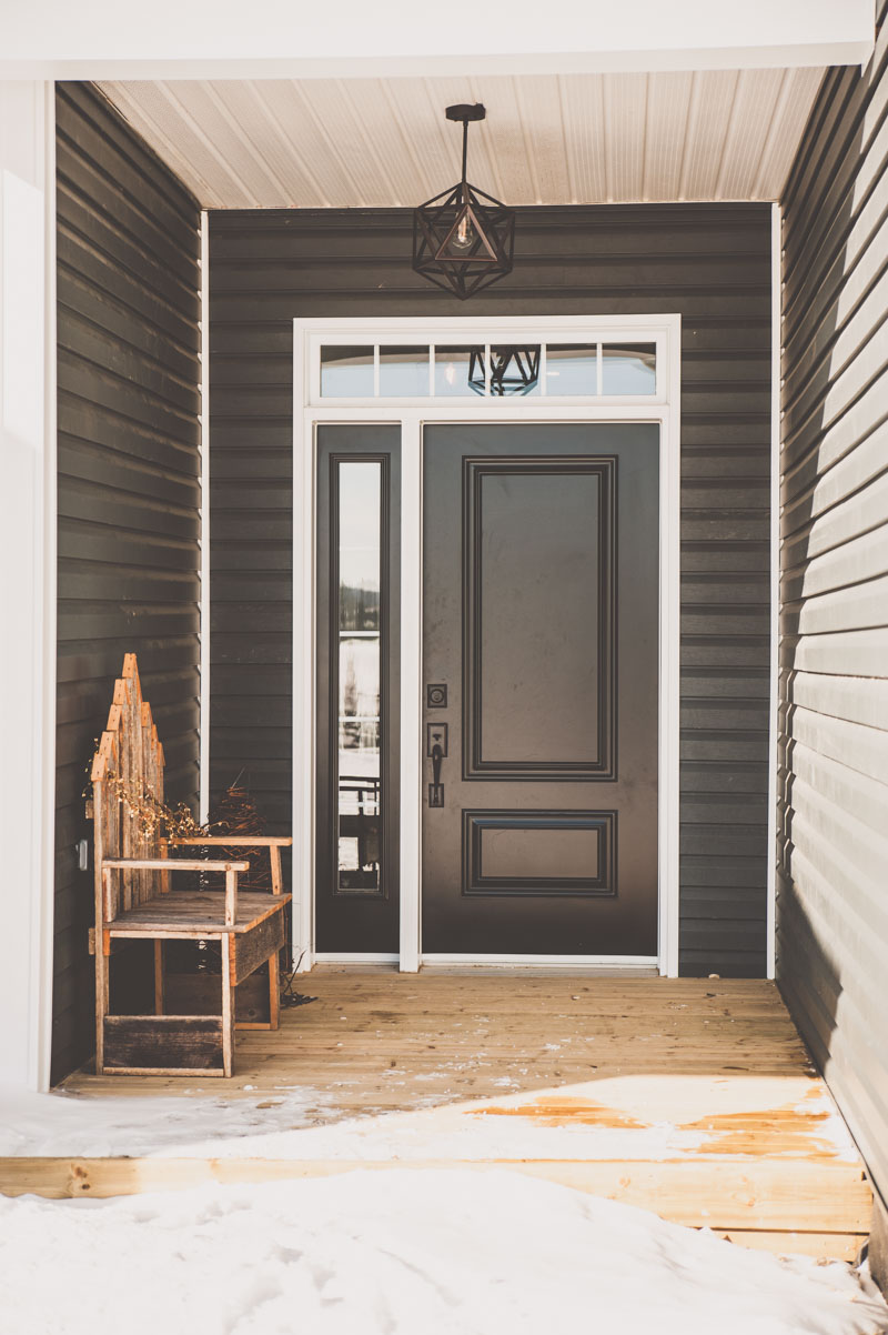 The black front entrance door is stately; flanked with a transom and sidelight