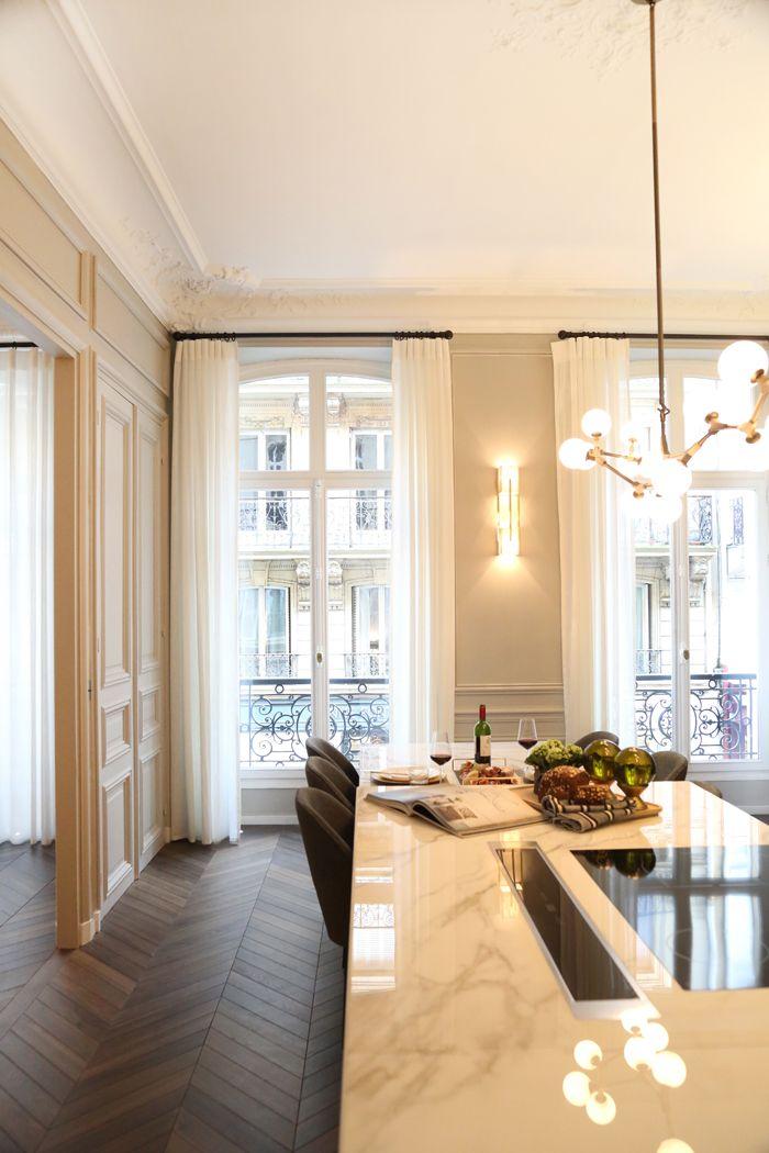 cocina de apartamento con mesa de marmol grandes ventanas aplique pared looshaus