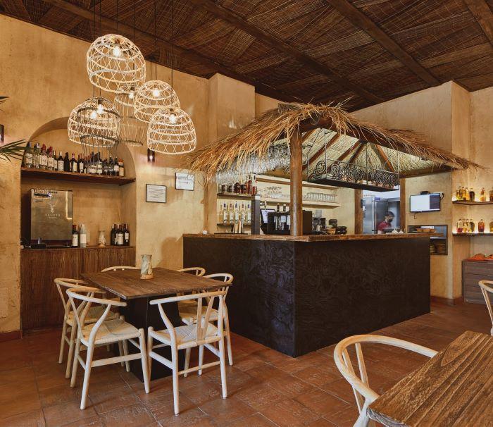Restaurante Quipu de Almería con una gran barra de piedra con techo de paja