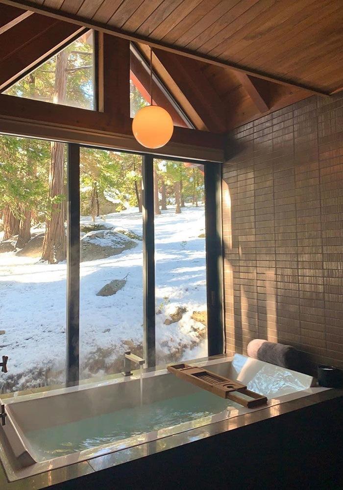 Baño con bañera y cristalera con vistas a la montaña