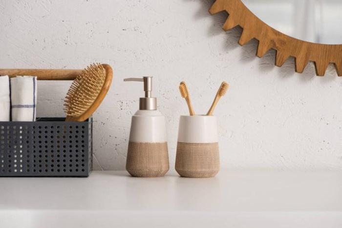 Recipiente de jabón, cepillos de dientes de madera y peine de madera en baño