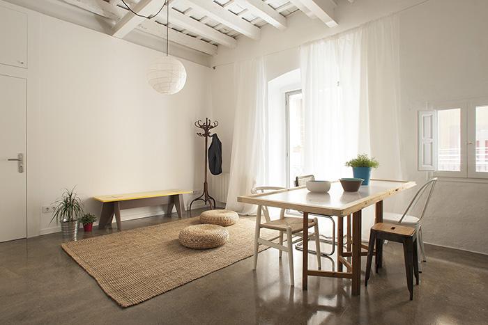 Salón luminoso y decorado al estilo nórdico mediterráneo, propio del proyecto Twin House por Nook Architects