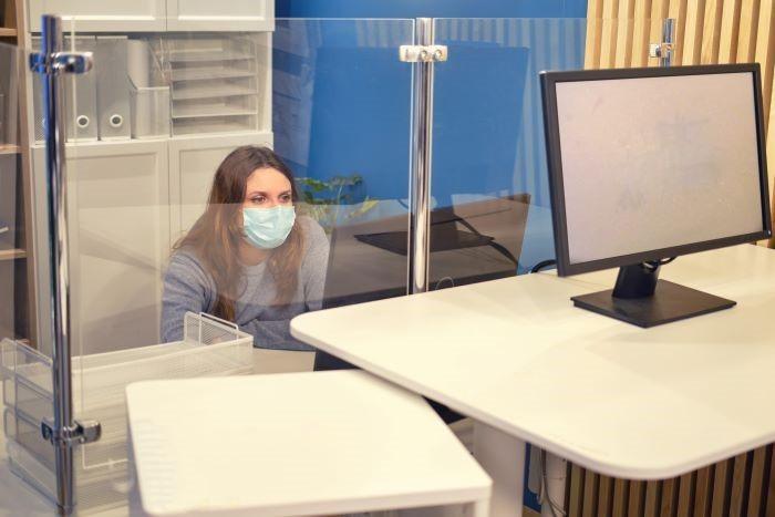 Mujer-detras-de-una-mampara-protegiéndose-del-virus