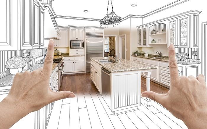 manos que dibujan en un cuadrado un diseño de cocina imaginario a partir de un plano