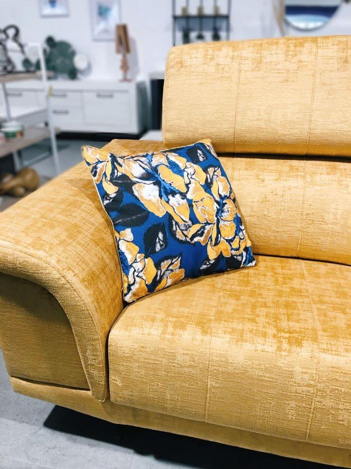 Sofá con un color vivo y encima un cojín estampado colorido