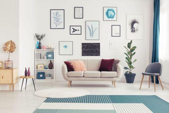 salón con muchos cuadros en la pared encima del sofá