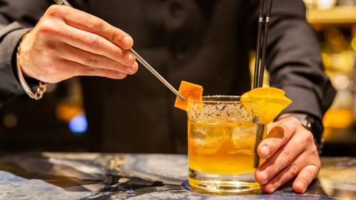 camarero sirviendo copa coctel pajitas