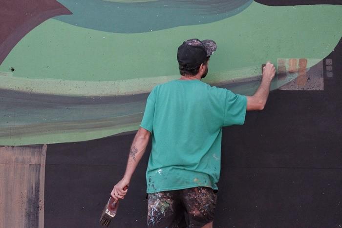 hombre pintando mural verde