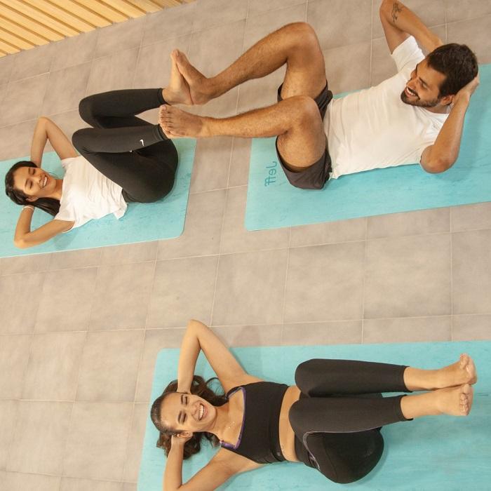 pareja y mujer haciendo ejercicio sobre una esterilla