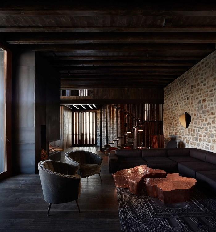 salón con un gran sofá clásico en contraste con lo demás más natural