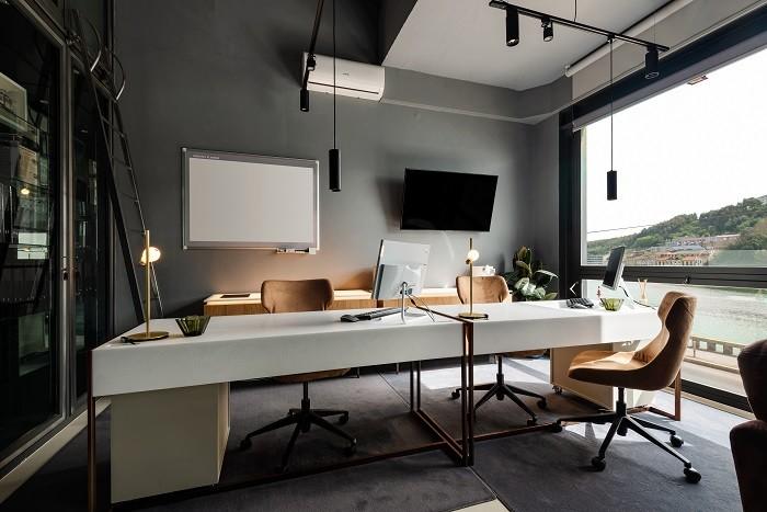 amplio despacho con mesa blanca y decoración industrial