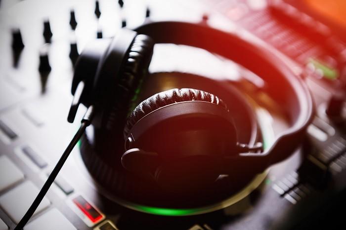 cascos de dj encima de una mesa de mezcla para hacer música