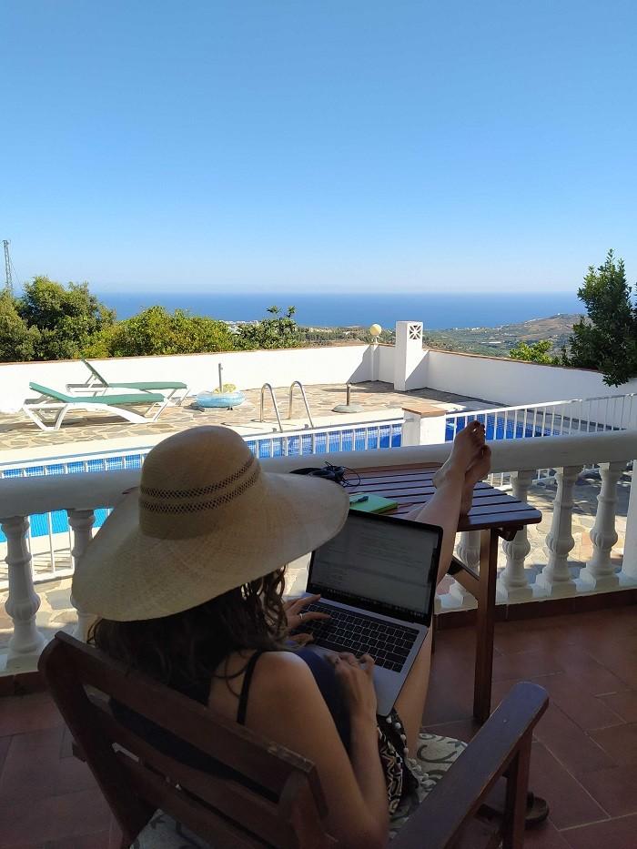 mujer en una terraza con piscina y al fondo el mar