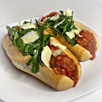 Chicken Meatball Sub topped with Arugula and shaved Parmesan Cheese