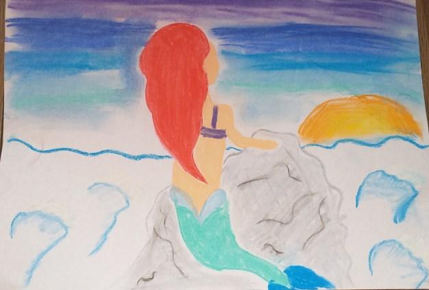 Zdjęcie przedstawia rysunek, któryzajął II miejsce, widać nanim Małą Syrenkę, którasiedzi naskale przybrzeżnej, wpatrując się wzachód słońca