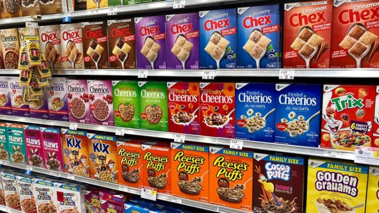 Picture of boxes of cereal on the shelf in a grocery store.