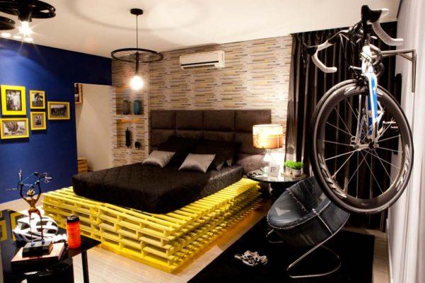 Base da cama feita com pallets e luminária a partir de roda de bicicleta no quarto do Rapaz, assinado por Lorena Coura e Rosemari Bragança