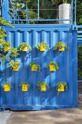 Complexo da Recepção Multiuso, assinado por Thiago Herrera, reaproveita a estrutura de um contêiner. Floreiras feitas a partir de latas de tinta vazias