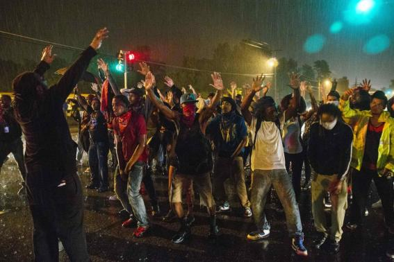 Protesters gesture as they stand in a street in defiance of a midnight curfew meant to stem ongoing demonstrations in reaction to the shooting of Michael Brown in Ferguson, Missouri August 17, 2014. REUTERS/Lucas Jackson